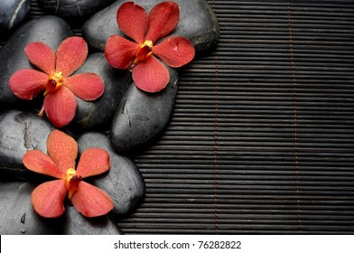 Red three orchid and zen Stones on bamboo mat