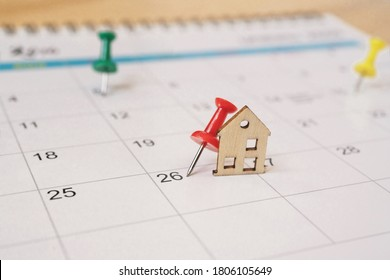 red thumbtack with miniature wooden house on white calendar