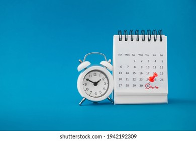 red thumbtack pin on the last day  of month with circle and pay day word near white analog clock on grunge blue background for business and finance concept