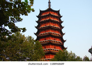 red tiered octagonal-base tower with multiple eaves in traditional Chinese architectural style; ancient Beisi Pagoda at sunset, China, bottom view