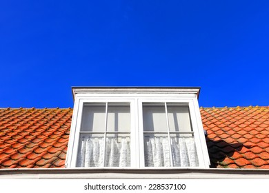 Red tile roof with attic window blue sky background