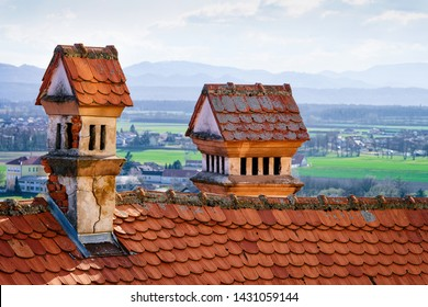 Red tile roof with chimneys in Ptuj Castle in Slovenia. Fragment of Architecture of Ptujski grad in Slovenija.