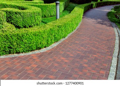 a red tile walkway along the hedge of trimmed green bushes.