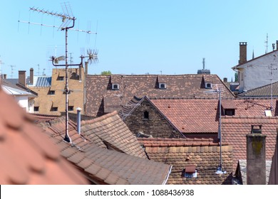 Red tiled rooftops in a town with television and radio antennae in an elevated view against a clear blue sky