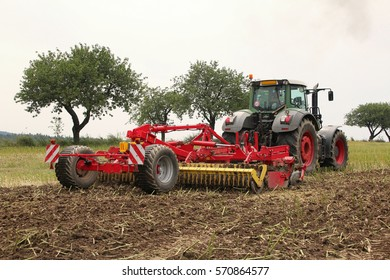 Red tilling tool in rape stubble attached to green tractor, preparing soil for fertilizing and seeding of wheat on field certified as bio arming, side perspective, cloudy autumn day