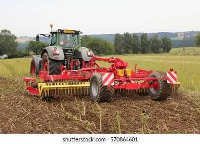 Red tilling tool in rape stubble attached to green tractor, preparing soil for fertilizing and seeding of wheat on field certified as bio arming, back perspective, cloudy autumn day