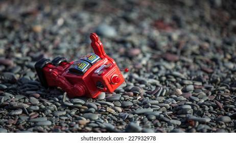 Red Tin Robot fallen on rocks