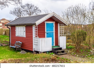 Red tiny house or shed at a plot of an allotment. Early spring time. Small red shack with blue door, white frames, shutters and metal forged bench by wall. Hut painted in traditional Swedish red color