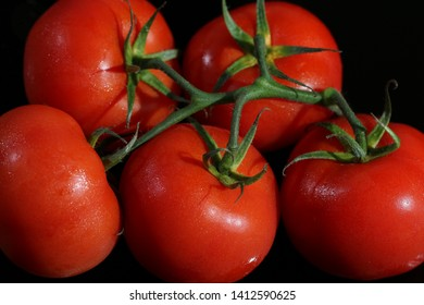 Red tomato with green little branches and leaf. It has few drops of water