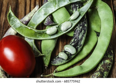 A red tomato and green string beans on a wooden background