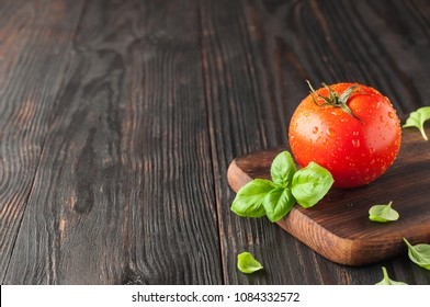 Red tomato on a cutting board with basil leaves on wooden background. Copy space. Fresh tomato wased for cooking. Tomato with droplets of water,