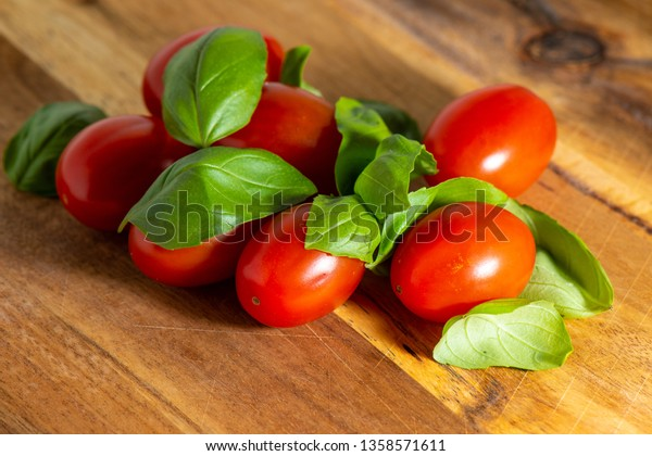 Red tomato on a cutting board with basil leaves on wooden background.