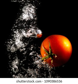 Red tomato in water on a black background