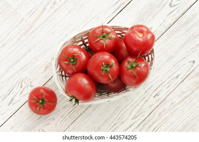 Red tomatoes in the basket on white wooden background. Copy space. Close up perspectives