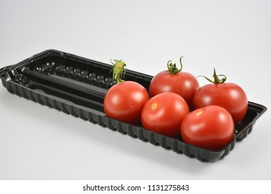 Red tomatoes in a black tray on a white background