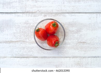 Red tomatoes in bowl on wood