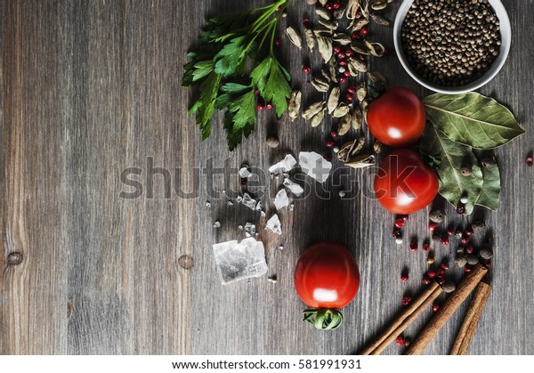 Red tomatoes and dry different spices with pieces of rock salt for cooking on wood background