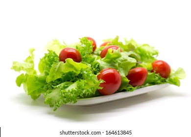 Red tomatoes and green lettuce on the white plate.