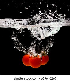 Red tomatoes with green twig in water splash