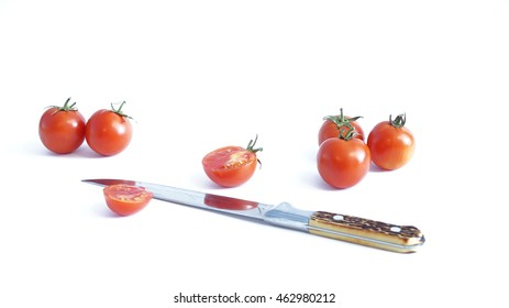 A red tomatoes lie on a white background next to a knife