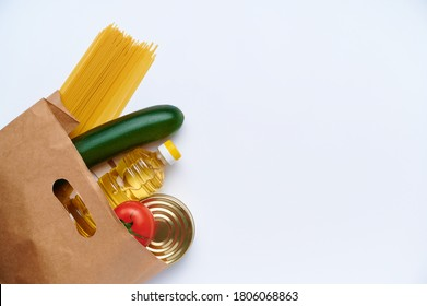 Red tomatoes, pasta, zucchini, yellow pepper, canned food, sunflower oil in paper bag. Fresh vegetables in the bag, top view flatlay on white background. The concept of healthy diet