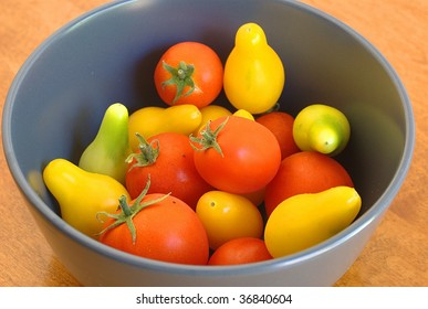 Red tomatoes with ripe and unripe yellow pear tomatoes in a bowl