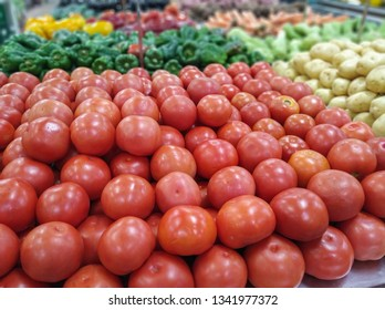 red tomatoes for sale in supermarket in hortifruti section, with unfocused background