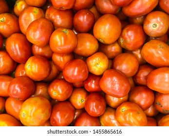 Red tomatoes (vegetable that rich of vitamin) sale on the basket in the supermarket shelf.