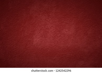 Red tone wall texture abstract background. Christmas background with copy space and darker vignette.
