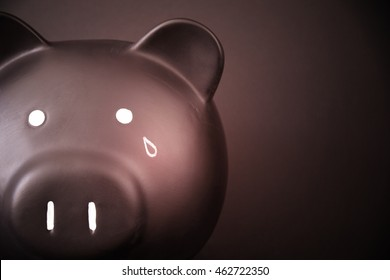 Red toned image of a piggy bank with a tear