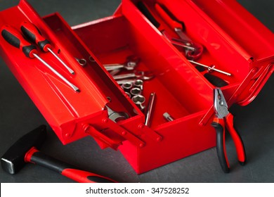 Red toolbox with metal work wrench kit of repairman. Pliers, hammer and many other chrome tools for automobile repair on workshop background