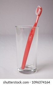 Red toothbrush in a glass tumbler against a plain backing.