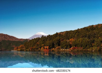 Red torii gate on the shore of Lake Ashi, near Mount Fuji in Hakone, Japan.