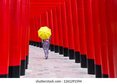 Red Torii gates with woman in kimono holding yellow umbrella at Hinoki land Landmark at Chaiprakarn, Chiang Mai, Thailand