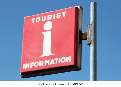 red tourist information sign against blue sky