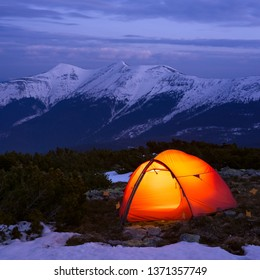 Red tourist tent in spring mountains