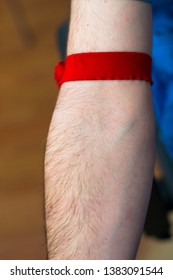 the red tourniquet on a man's hand