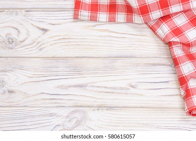 Red towel over wooden kitchen table. View from above with copy space.