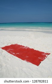 red towel for sunbath on beach,  beautiful sand surface background