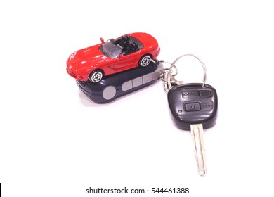 Red toy car and black car keys on white background