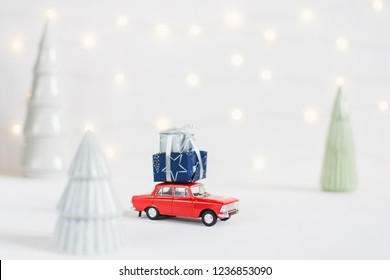 Red toy car with a christmas presents on the roof, garland bokeh on the background, shallow depth of field.
