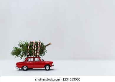 Red toy car with a christmas tree on the roof, white background, shallow depth of field.