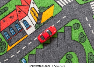 Red toy car on a city themed carpet. City traffic concept