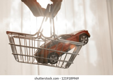 red toy car in shopping cart. cheap used cars, sell a car concept. sunrise background