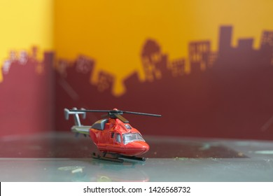 Red toy single  blade helicopter on blur city background