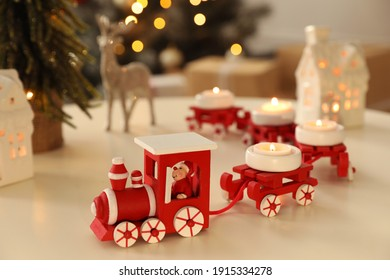 Red toy train as Christmas candle holder on white table in room
