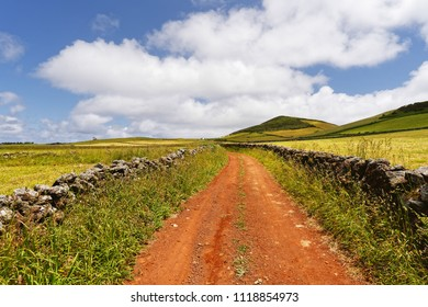 A red track leads through a hilly landscape, on the edge of natural stone walls, great depth, sky with some clouds - Location: Azores, island of Sao Jorge