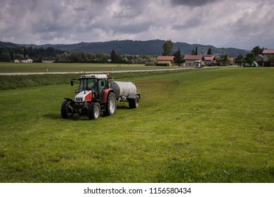 A red tractor with a cistern trailer spreading or dispersing manure or fertilizer on a green field in Austria on a cloudy day.