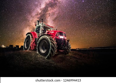 Red tractor with colorful christmas lights. Milkyway background. Agricultural machinery with Christmas atmosphere.