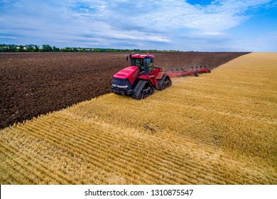 red tractor cultivates the land for planting crops.Farmer in tractor preparing land with seedbed cultivator as part of pre seeding activities in early spring season of agricultural works at farmlands.